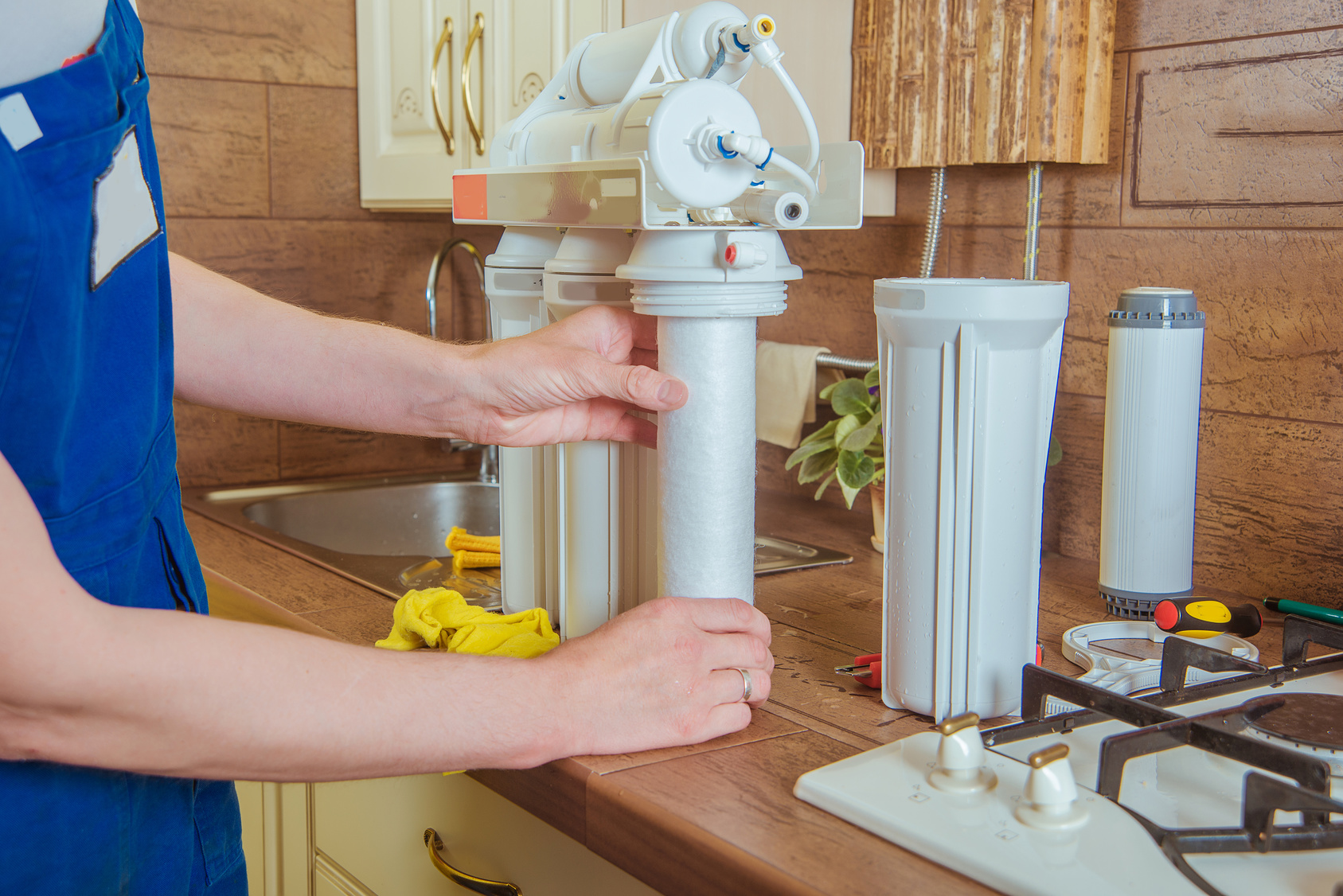 plumber installing new water filter in the kitchen