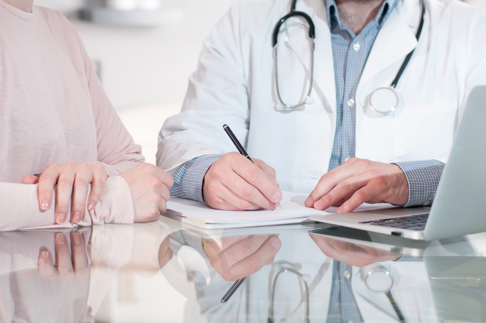 Doctor is writing prescription to patient