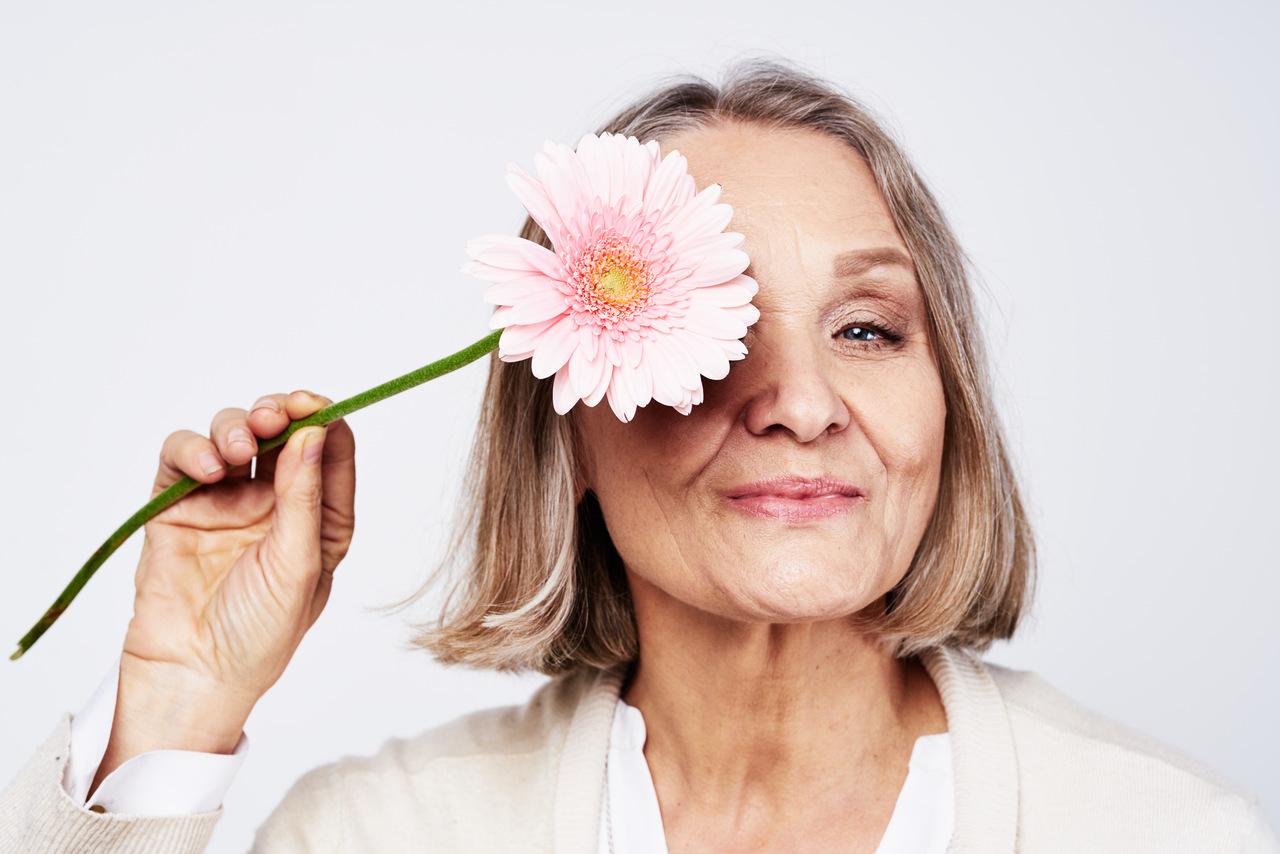 Menopauza - piękna, dojrzała kobieta trzymająca kwiat.